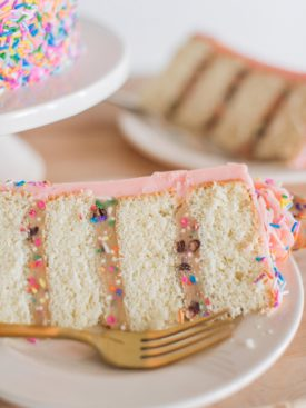 Sprinkle Cookie Dough Cake - tender white cake layers with chocolate chip and sprinkles cookie dough and vanilla buttercream. #cakebycourtney #birthdaycake #cookiedoughcake #sprinkles #cake #easycakerecipe