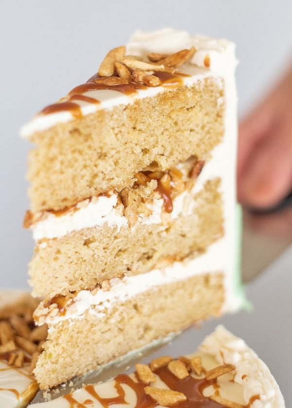 Inside look at the apple cake layers, almond white chocolate buttercream, candied almonds and salted caramel