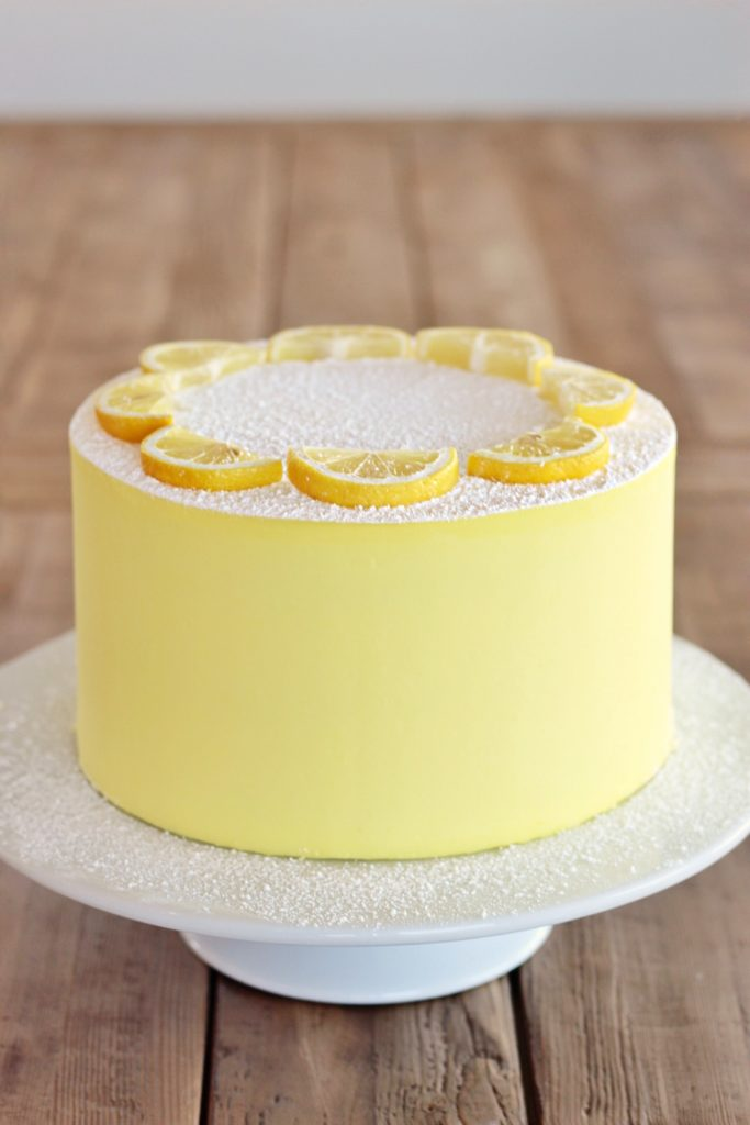 Round yellow lemon cake on top of spinning cake table.