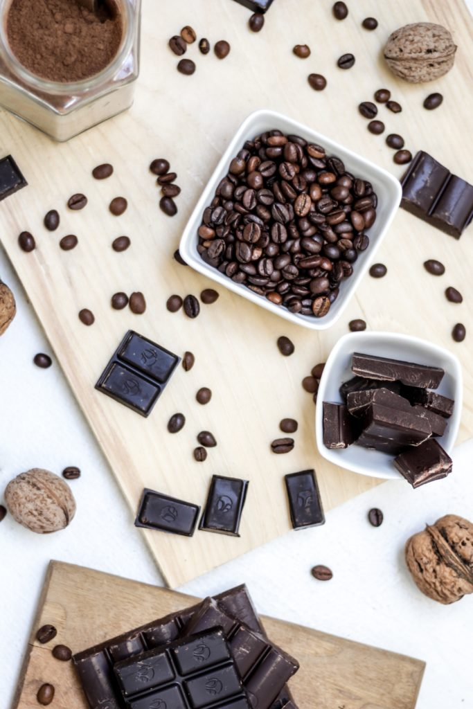 Wooden board displaying a variety of chocolates and cocoa beans for a tasting.