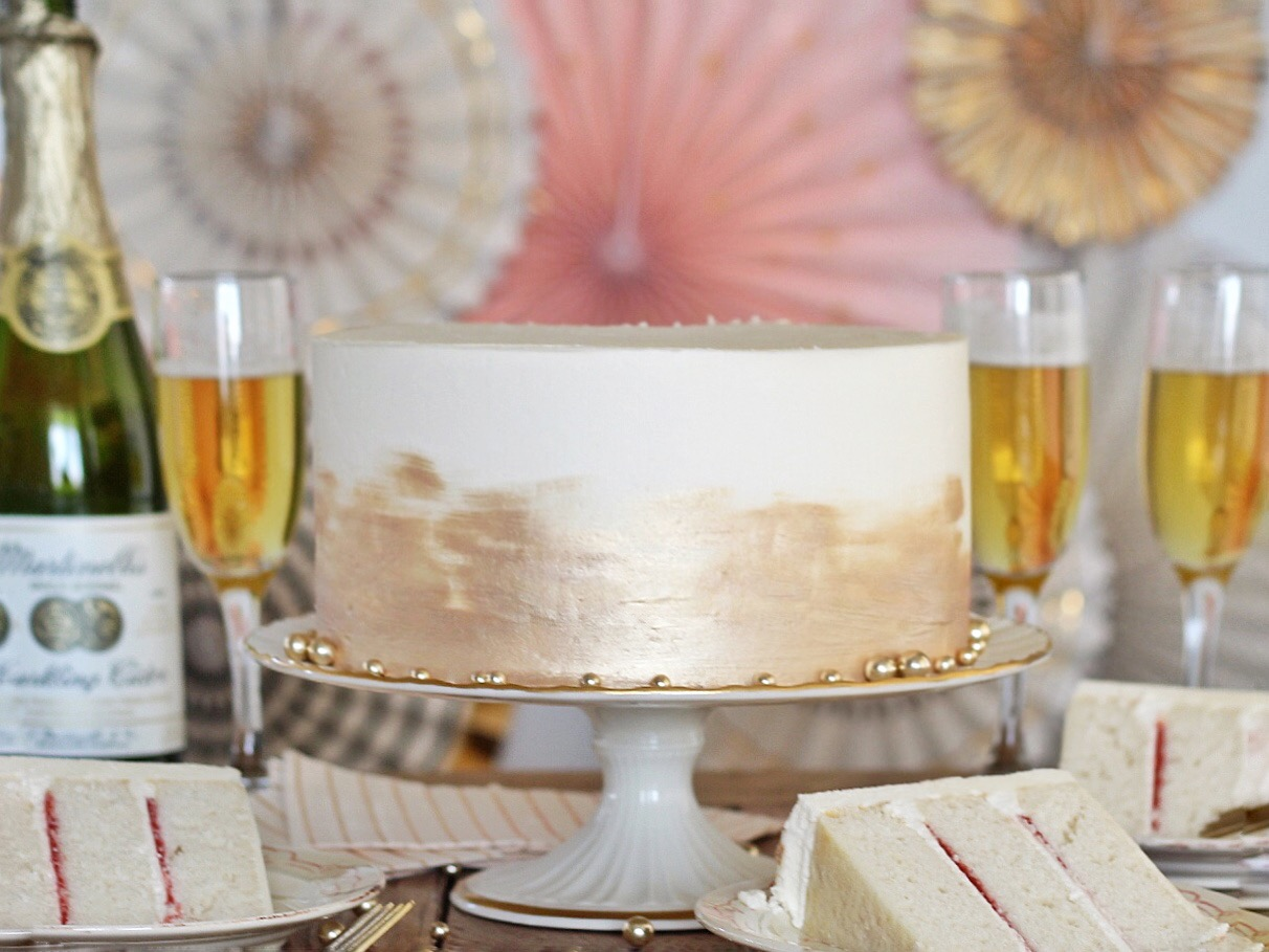 "Champagne Cake - champagne inspired cake with tender, ""champagne"" cake layers, a raspberry peach puree filling and a champagne buttercream.  #cakebycourtney #champagnecake #newyearsevecake #cake #easycakerecipe #thebestchampagnecake #pinkchampagnecake #newyearsevedessert"