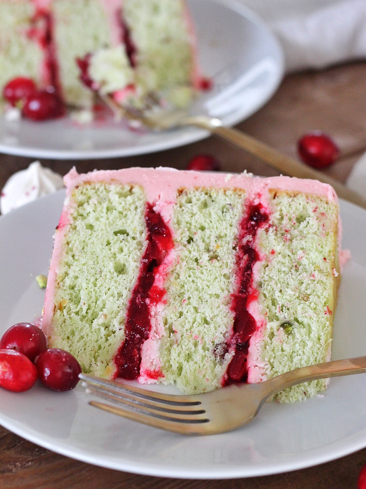 Pistachio Cranberry Cake - Pistachio cake layers with cranberry compote and cranberry buttercream. #cakebycourtney #pistachiocranberrycake #pistachiocake #cranberry #christmascake #easycakerecipe