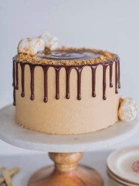 The ultimate s'mores cake for peanut butter lovers! Graham cracker cake layers with a toasted marshmallow filling, toasted graham crackers, chocolate ganache and peanut butter buttercream.