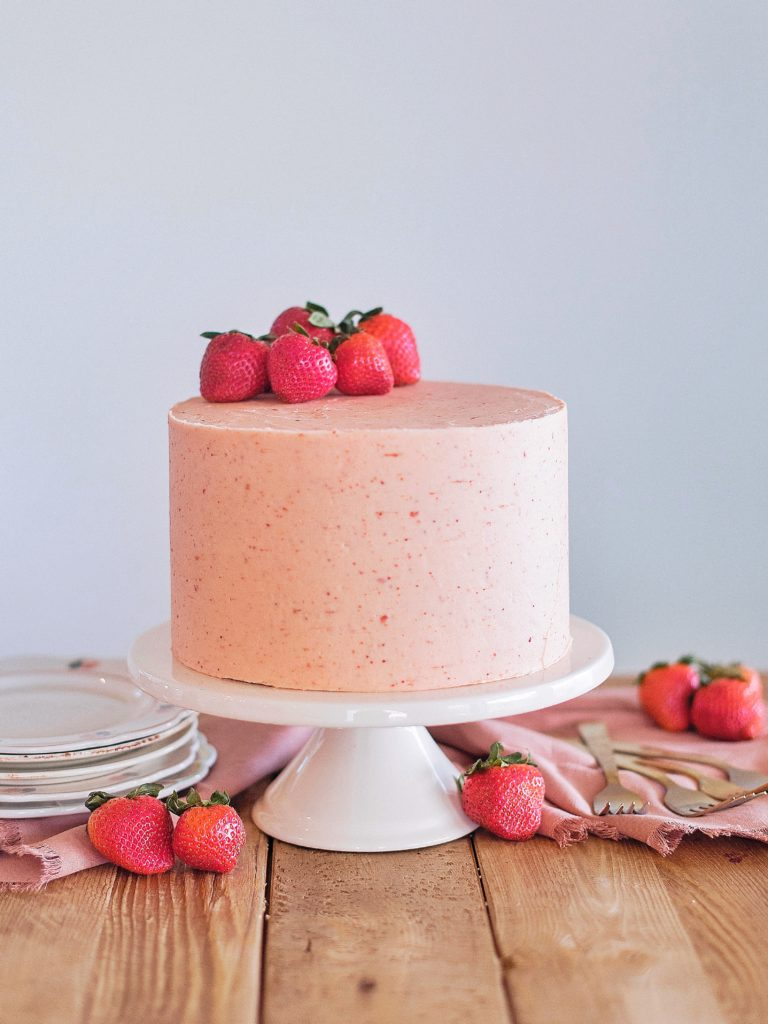 Strawberry Shortcake: Tender and fluffy layers of vanilla cake, filled with whipped cream and fresh strawberries, and covered in a strawberry buttercream. #cakebycourtney #cake #cakerecipe #strawberryshortcake #shortcake #strawberry #buttercream