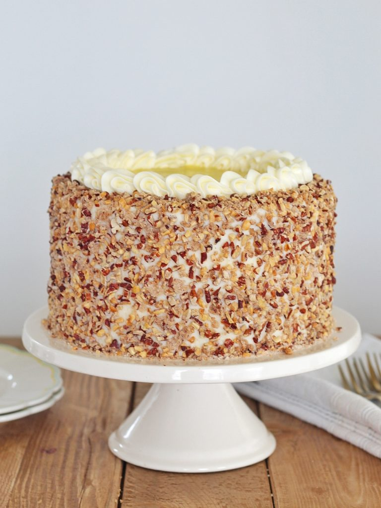 Hummingbird Cake: layers of banana and pineapple spice cake, pineapple curd, cream cheese buttercream and toasted candied pecans. #cakebycourtney #hummingbirdcake #cake #hummingbirdcakerecipe #creamcheesefrosting #creamcheesebuttercream #pineapplecurd #pineapple