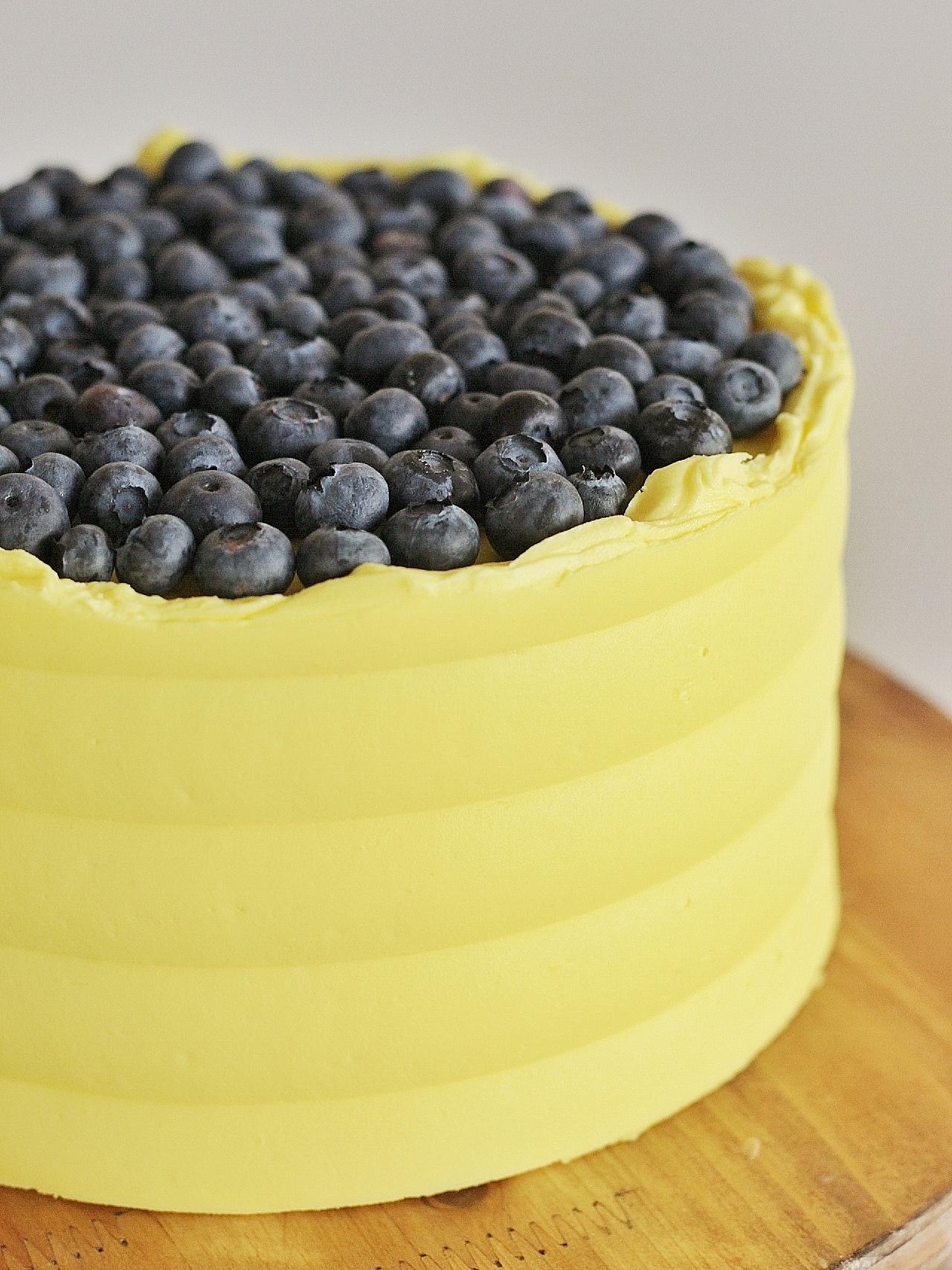 Lemon Blueberry Cake - tender lemon cake layer with fresh blueberries, lemon curd and lemon buttercream. #cakebycourtney #lemoncake #lemonblueberrycake #lemondessert #lemoncurd #easylemoncake
