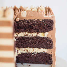 Chocolate Banana Peanut Butter Cake - think #ChunkyMonkey ice cream but with peanuts instead of walnuts! This cake is moist and flavorful and a total crowd pleaser. You'll start with chocolate banana cake layers, add a peanut butter banana cream filling and then cover it in chocolate and peanut butter buttercreams. #cakebycourtney #chocolatecake #chocolatebananacake #chocolatepeanutbutter #buttercream #easychocolatecakerecipe #cake #peanutbutterbuttercream #banana