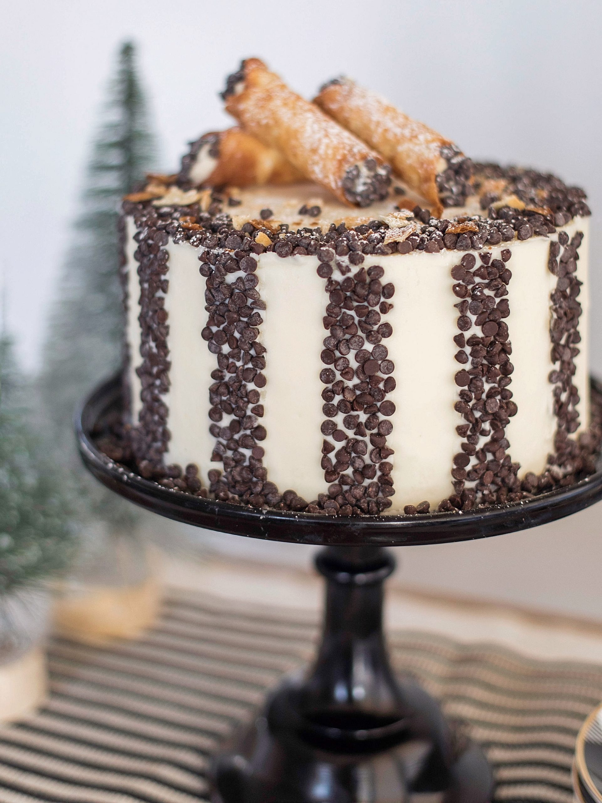 Delicious white cake layers with a hint of cinnamon, a creamy sweet ricotta filling with chocolate chips and vanilla buttercream. #cannoicake #cannolirecipe #homemadecannoli #christmascake #christmasdessert #holidaydessert #christmasdessertideas #christmascakeideas #cakebycourtney
