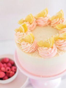Coconut Lemon Raspberry Cake - coconut cake layers, lemon curd, raspberry cream filling, and coconut buttercream. #cakebycourtney #coconutcake #bestcoconutcake #lemoncurd #raspberrycream #raspberryfilling #coconutbuttercream #summercake #bestsummerdessertrecipes #summercakes #summerdessertrecipes