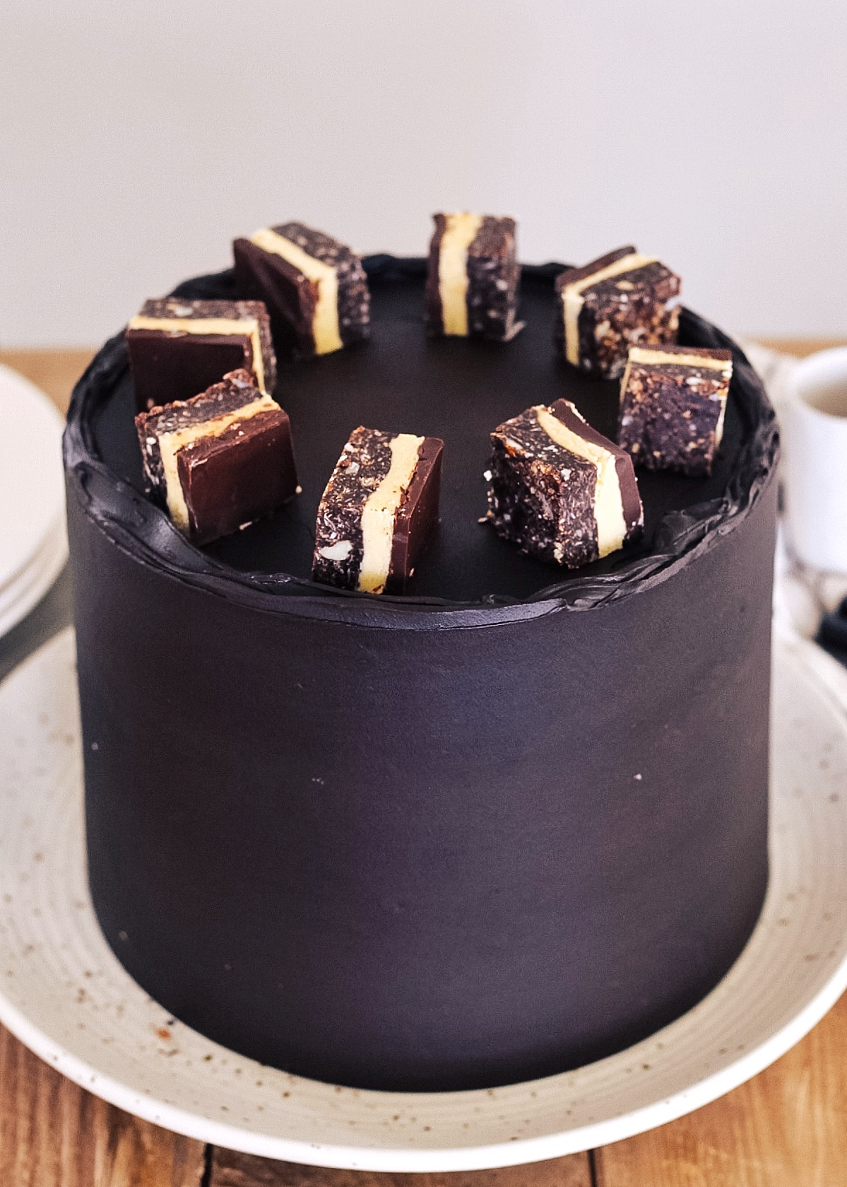 Nanaimo Bar Cake - the most delicious chocolate cake layers baked on a graham cracker, almond, coconut, and chocolate crust, with a custard filing and covered in a chocolate fudge buttercream. #cakebycourtney #nanaimobarcake #nanaimobarcakerecipe #cakerecipe #chocolatecakerecipe #fudgebuttercream #bestcakerecipe #nanaimobars #nanaimobarrecipe