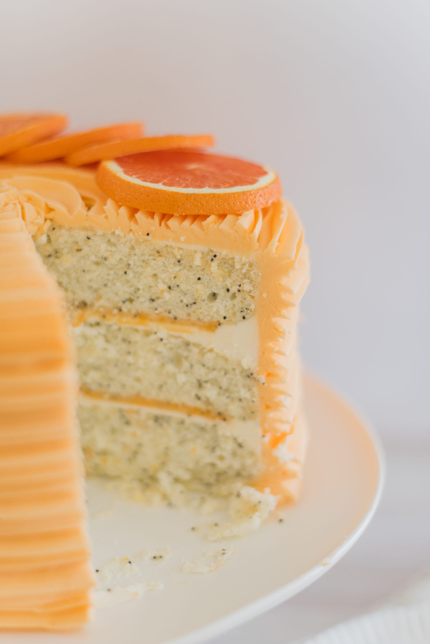 Orange Almond Poppy Seed Cake - light and fluffy poppy seed cake layers, infused with orange and almond flavoring, topped with almond buttercream and orange curd. #cakebycourtney #almondcake #almondpoppyseedcake #orangealmondpoppyseedcake #orangecurd #almondbuttercream #summercake #summerdessertrecipe #summerdessert #poppyseedcake #lightandfluffycake #cakedesign #cakerecipes #cakesforgirlsbirthday #cakeaesthetic #cakeideas #cakedecorating