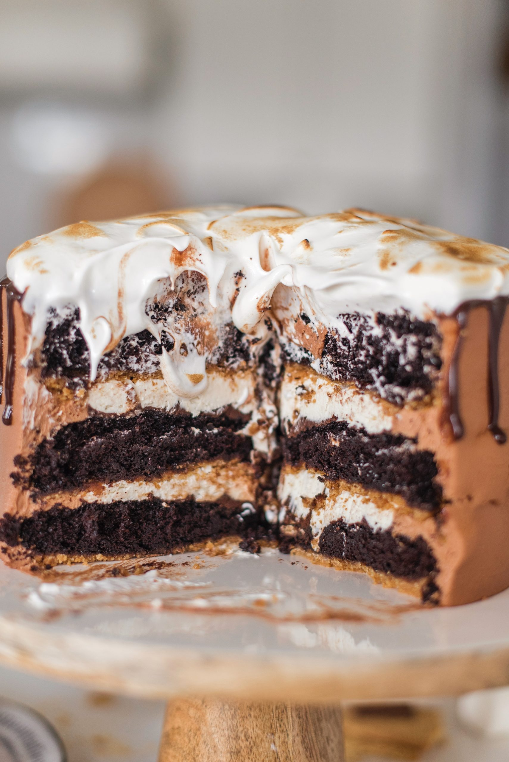 Ultimate S'mores Cake - the perfect cake for summer! Chocolate cake baked on graham cracker crust, filled with chocolate ganache, toasted marshmallow filling, chocolate buttercream and homemade marshmallow fluff. #smorescake #ultimatesmorescake #cakebycourtney #smores #smorescakerecipe #smoresdessert #summercake