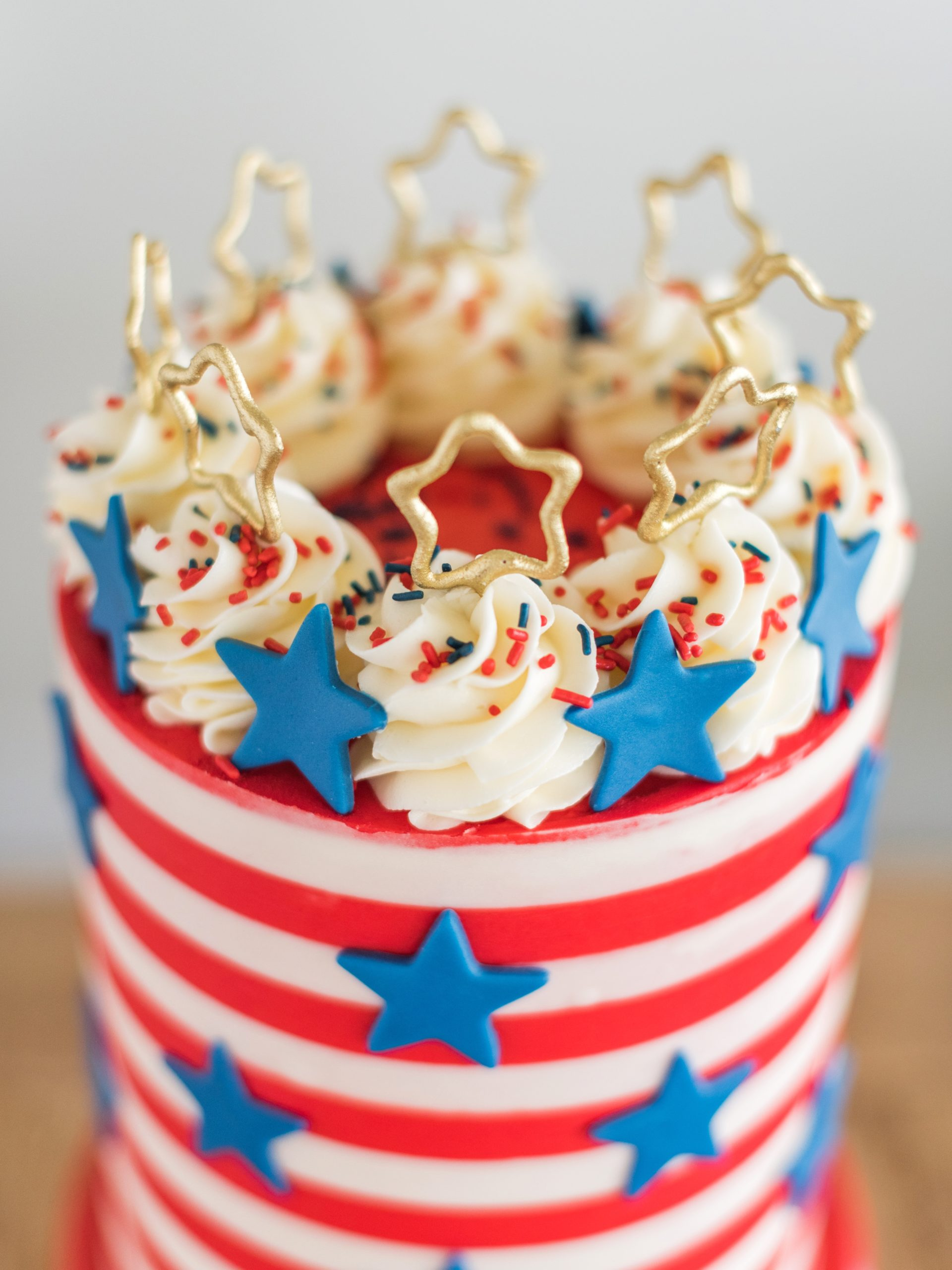 Sparkling Stars and Stripes 4th of July Cake -  how to create buttercream stripes and this 4th of July Stars and Stripes cake. #cakebycourtney #4thofjuly #fourthofjuly #fourthofjulycake #fourthofjulydesserts #4thofjulycake #4thofjulydesserts #4thofjulycakeideas #redwhiteandbluecake #starsandstripescake #howtomakebuttercreamstripes #howtocakeit