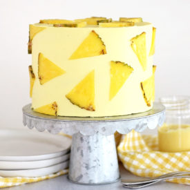 Pineapple Dole Whip Cake - the most delicious pineapple cake inspired by Disney's Dole Whip ice cream. This Pineapple Dole Whip Cake is filled with layers of pineapple cake, pineapple curd and pineapple buttercream #cakebycourtney #cake #pineapplecake #pineapplebuttercream #howtomakecake #summercake #pineapple #summerdessert #pineapplecakerecipe #cakerecipe #homemadeicing #homemadecake #howto makebuttercreamfrosting #frostingrecipe #buttercreamrecipe