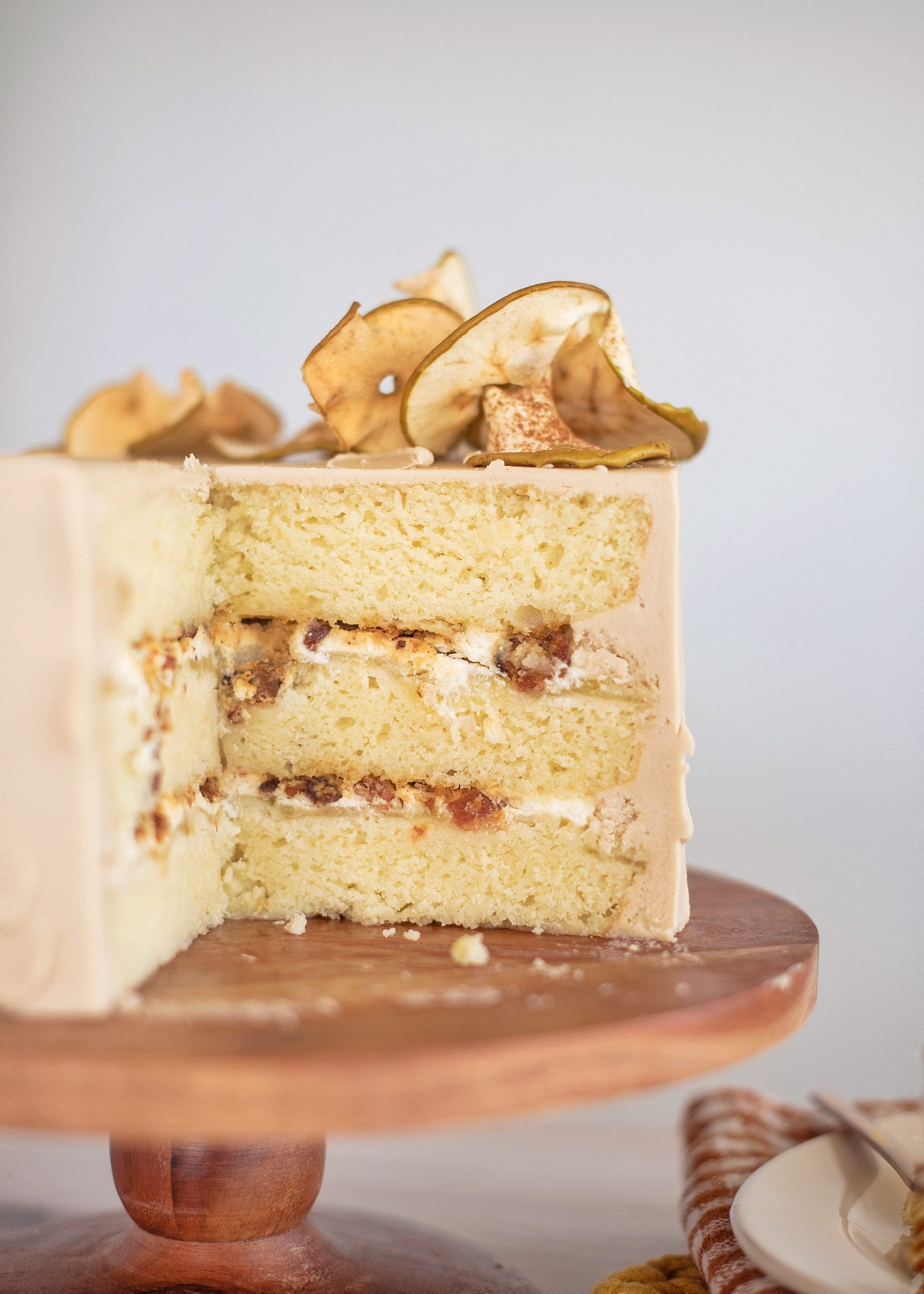 Sweet and Savory Apple Ricotta Bacon Cake with maple buttercream. The perfect pairing of sweet and savory flavors to kick off the fall season. Tender ricotta cake layers baked on tart green apples, layered with ricotta filling, candied bacon and maple buttercream. #bacon #cake #maple #maplebuttercream #candiedbacon #maplebacon #fallcakes #fallcakeflavors #fallcakerecipe #sweetandsavorydessert #bestfallcakeflavors #falldesserts #falldessert #ricottacake